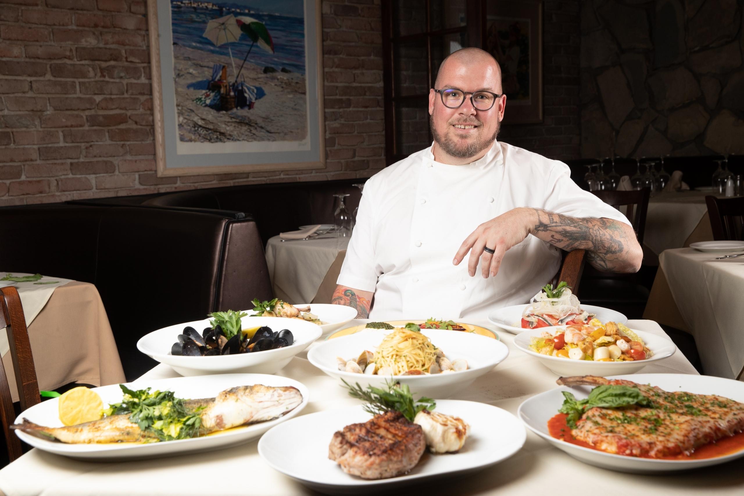 Piero's Italian Cuisine New Chef Chris Conlon Sitting at Table of Piero's Menu Favorites